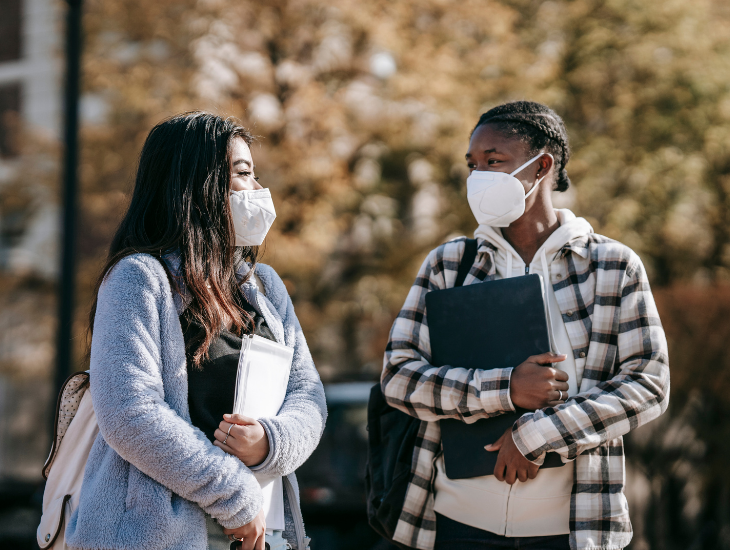 two masked students talking on campus