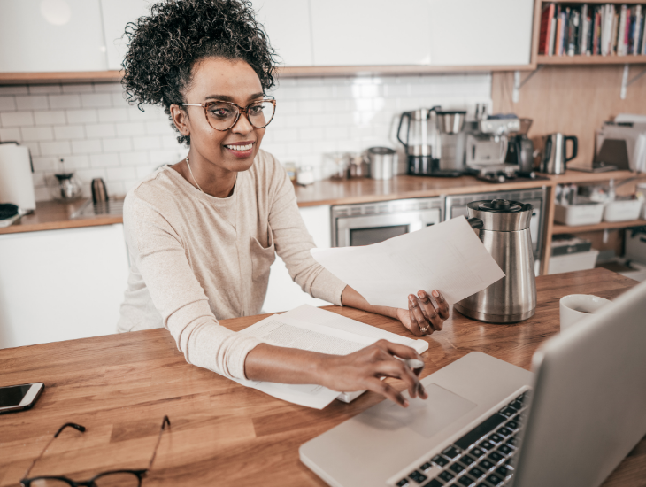 woman working on laptop organizing papers